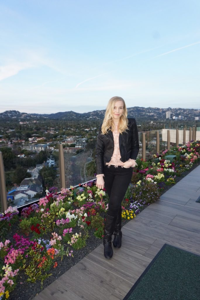 @blushinginhollywood wearing a blush pink feather top from Amazon with a faux leather jacket, black Good American Jeans, and Black boots at The Rooftop at JG in Beverly Hills