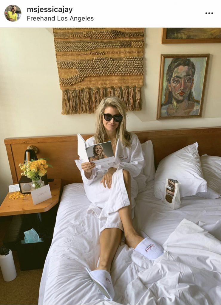 Jessica Jay reading her new favorite book- the Google photobook we made her for her bachelorette party - in bed at The Freehand DTLA